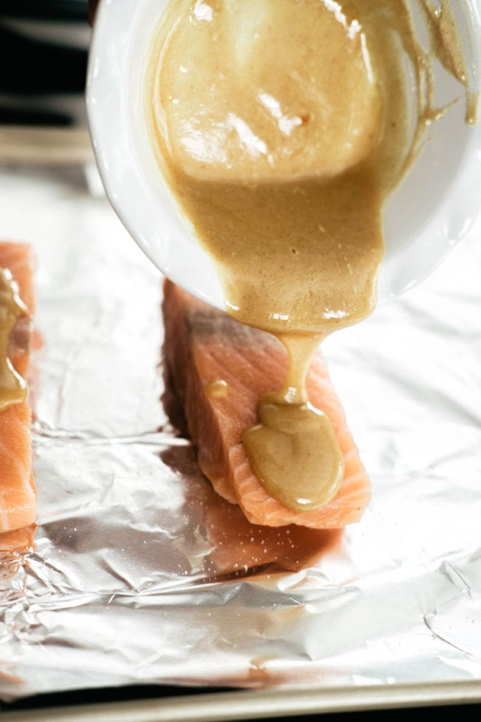 pouring honey mustard over salmon