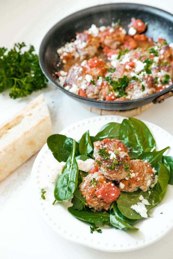 meatballs on a plate with salad and bread