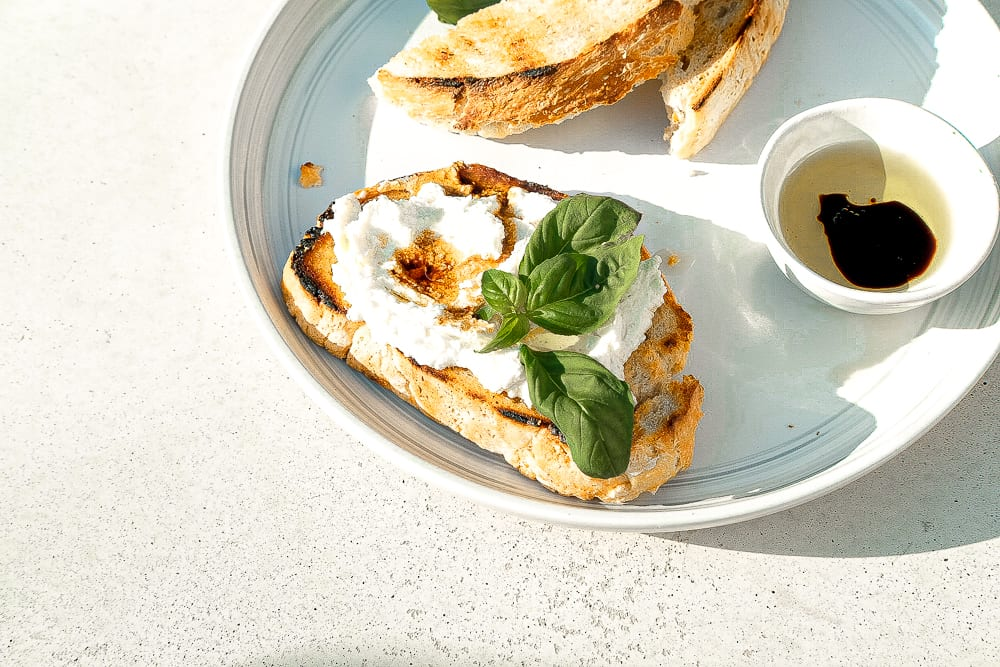 Grilled bread smeared with spicy goat cheese
