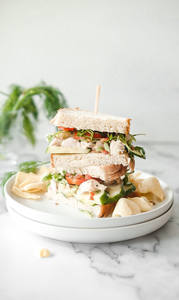 chicken salad sandwich cut in half and stacked.