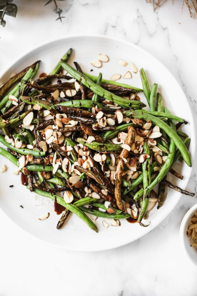 plate of crispy air fried green beans with balsamic dressing