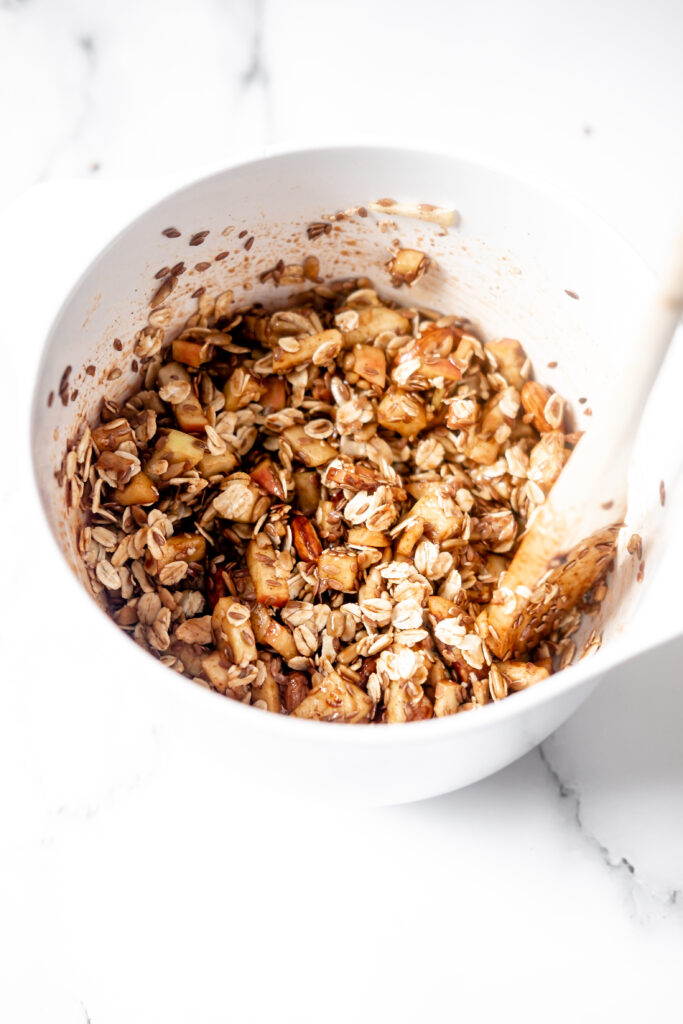 a spoon mixing granola in a white mixing bowl