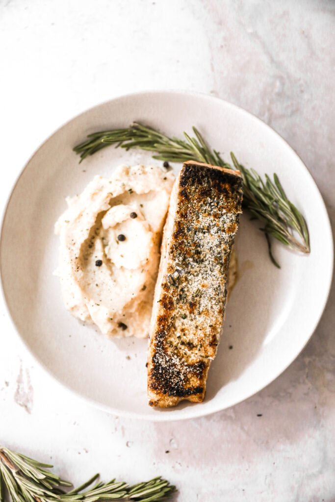 crispy salmon plated with rosemary and mashed potatoes
