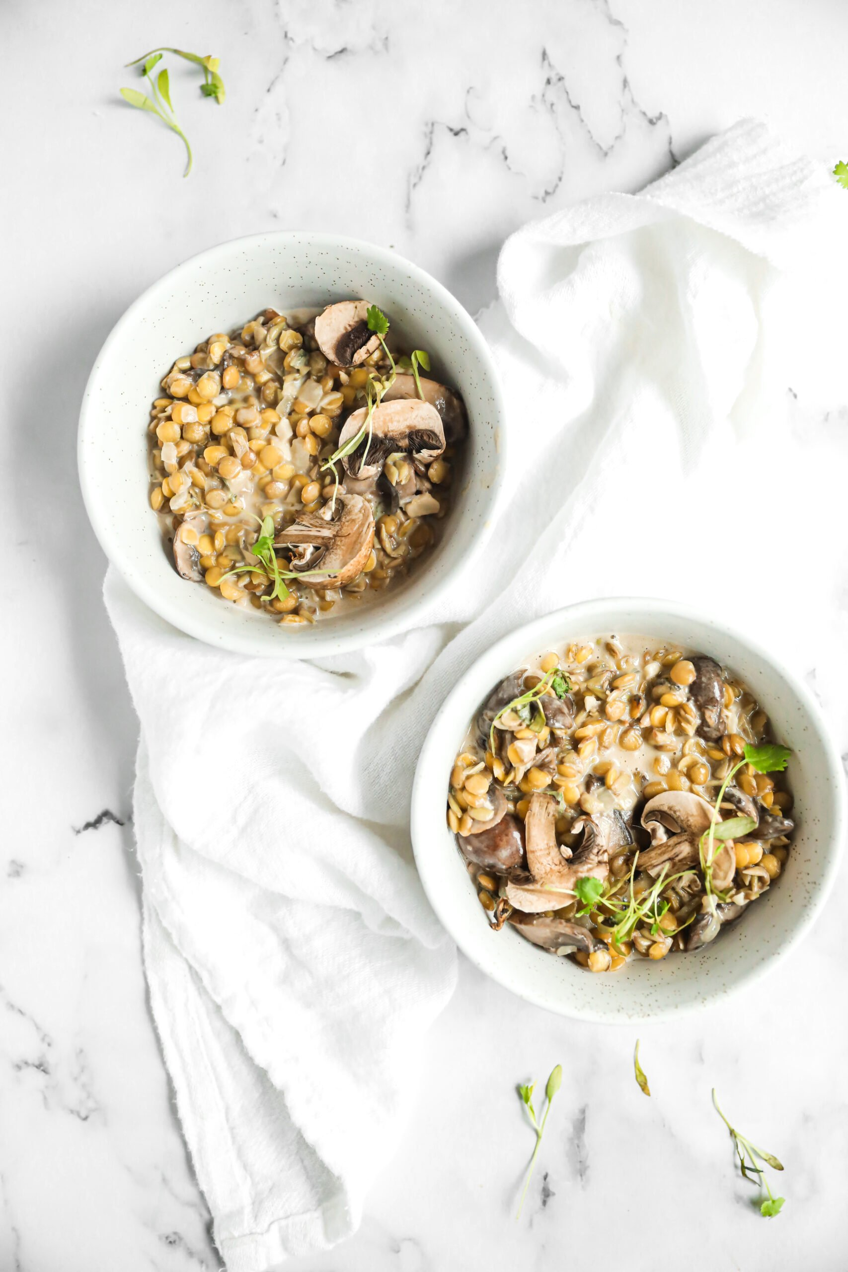 lentil risotto with mushroom and sage in 2 bowls with a white linen around them