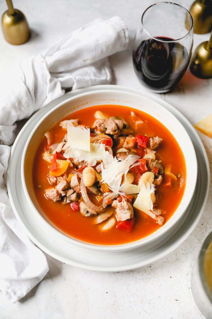 bowl of chicken cacciatore soup topped with parmesan.