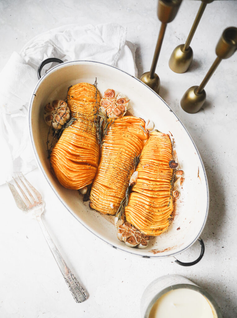 3 hasselback squash in a white roasting pan