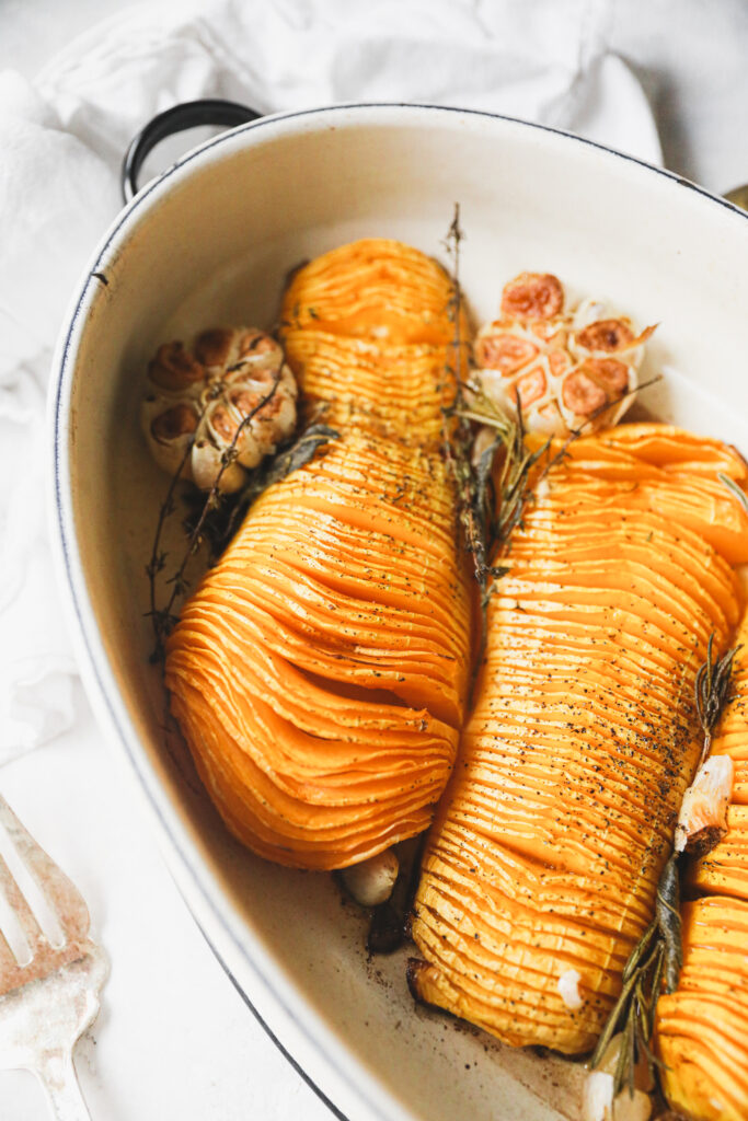hasselback squash in a roasting pan with garlic and herbs