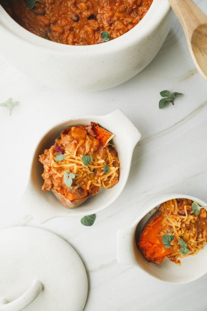 2 bowls of creamy pumpkin chili over sweet potatoes. Garnished with fresh oregano.