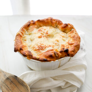 French Onion Pot Pie with white linen and wooden spoon