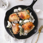 4 chicken thighs and onion in cast iron skillet with rosemary