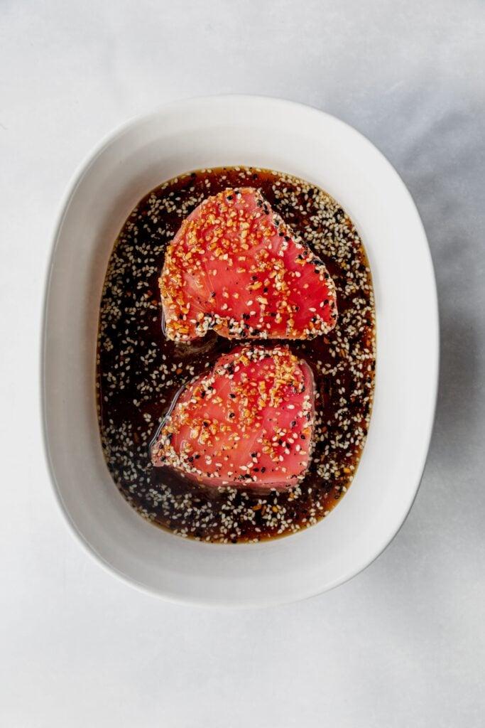 Ahi Tuna being marinated in a white dish