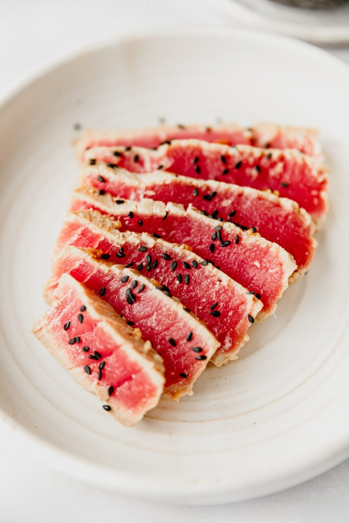 sliced seared Ahi Tuna garnished with black sesame seeds on a white plate