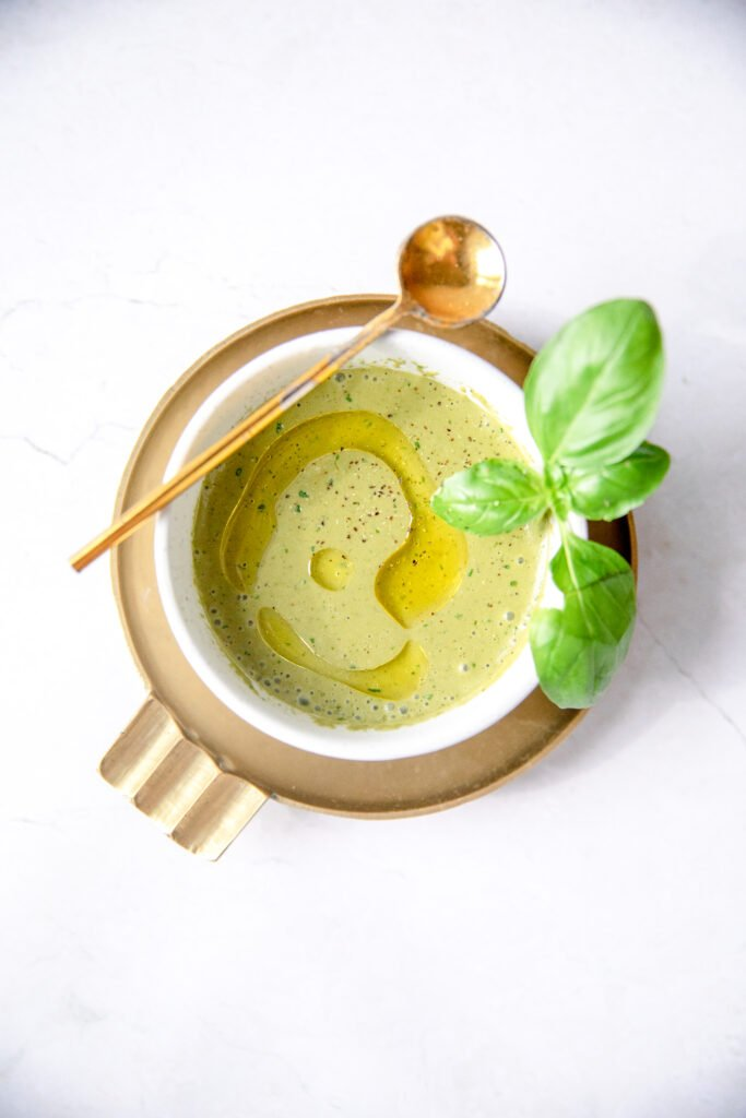 basil balsamic vinaigrette in a white bowl with gold tasting spoon