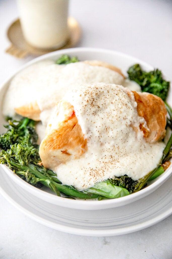 creamy cauliflower Alfredo sauce poured over chicken and broccoli
