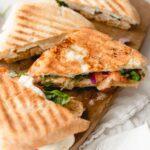 frontega chicken panini sandwich halves on cutting board