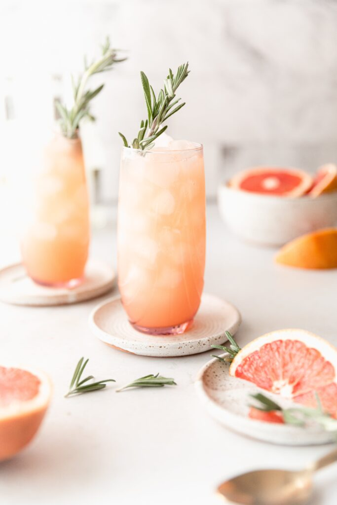 2 Moscow mules in pink clear cups surrounded by grapefruit and rosemary garnish