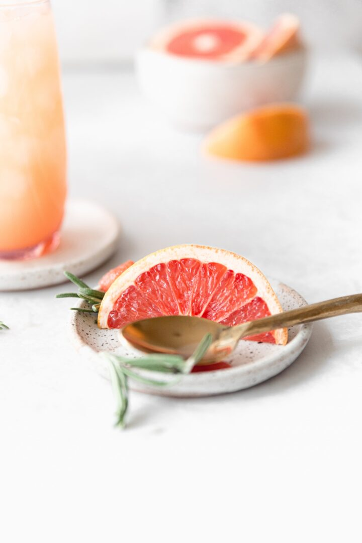 slice of grapefruit with a sprig of rosemary on a white plate with a gold spoon next to it