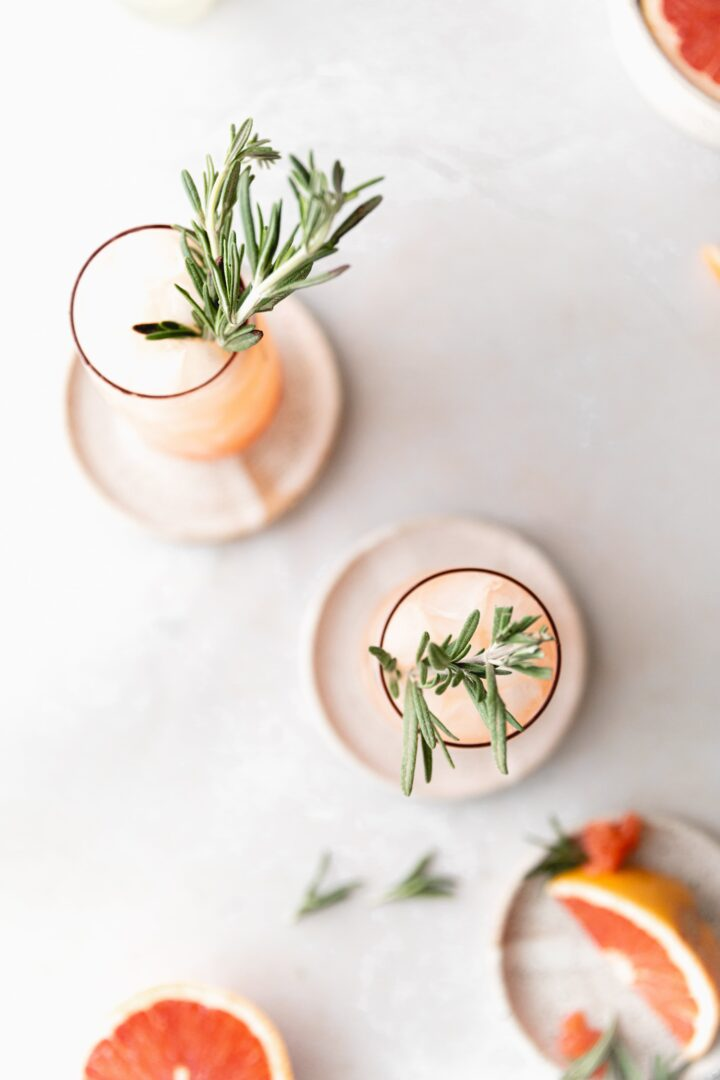 top down shot of 2 pink mules, focused on the rosemary garnish