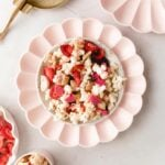 pink party Chex mix on a pink scalloped plate with other pink scalloped plates surrounding it