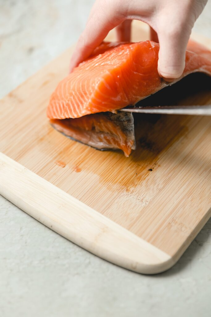removing salmon skin with a knife