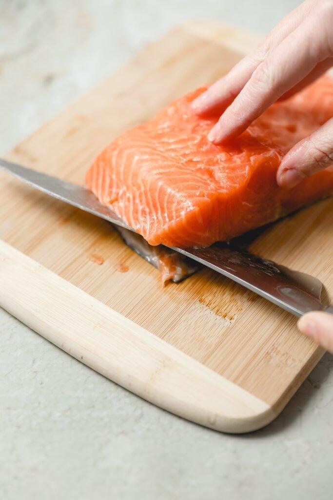 serrated knife slicing off salmon skin
