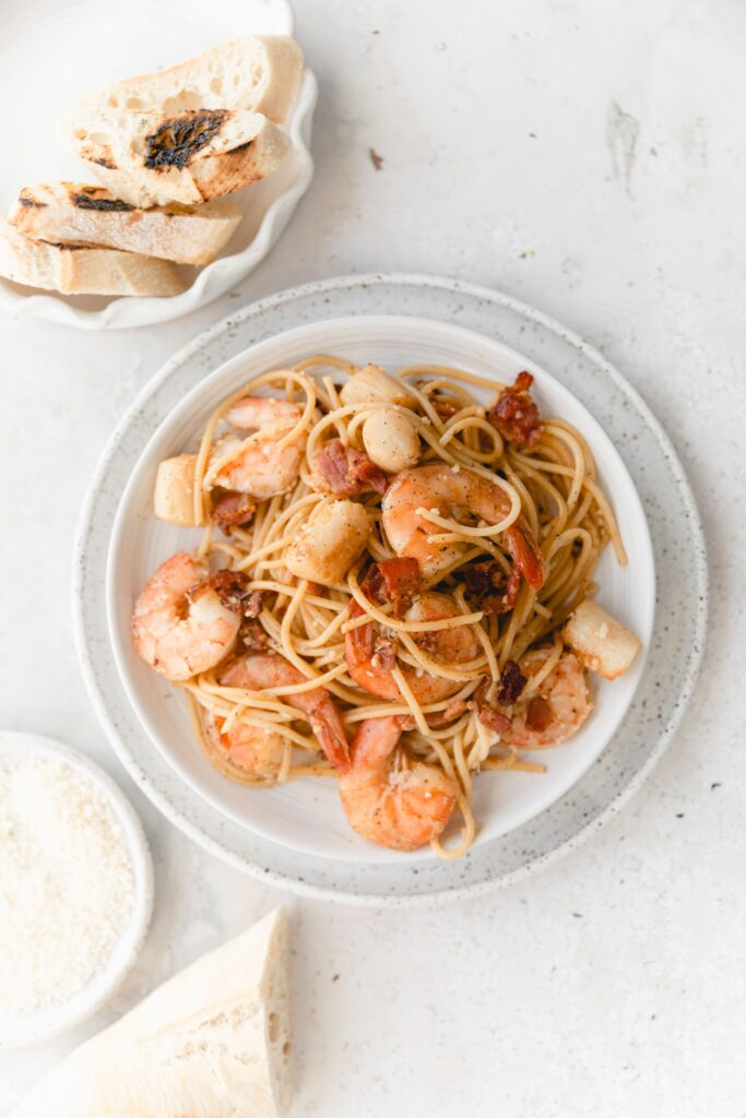 shrimp scallop pasta on white dishes served with bread