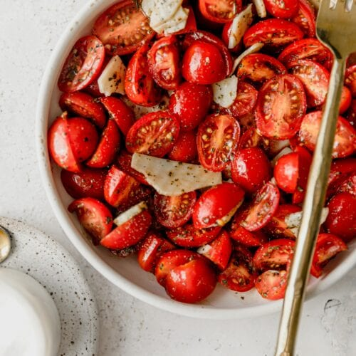 white bowl full of cherry tomatoes in Italian marinade with a gold fork