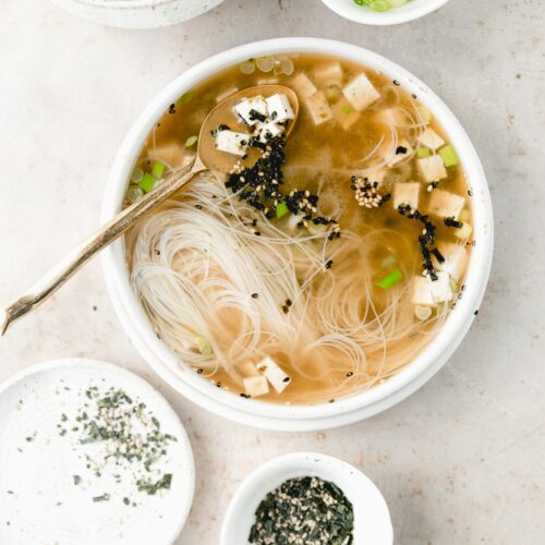 white bowl of miso soup with garnishes arranged around