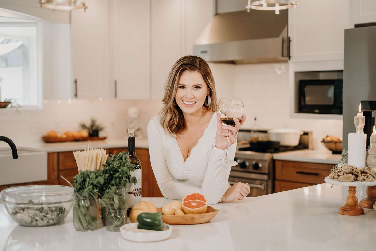 Sara ayes holding wine in a white kitchen with fresh ingredients around her