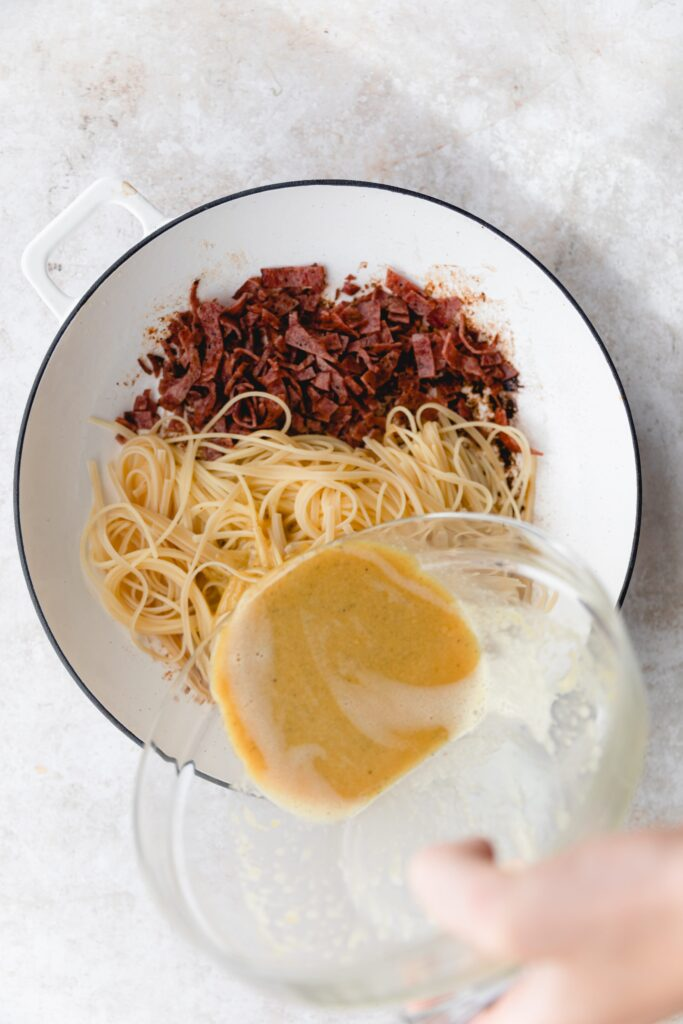 pouring the egg sauce over the pasta and bacon