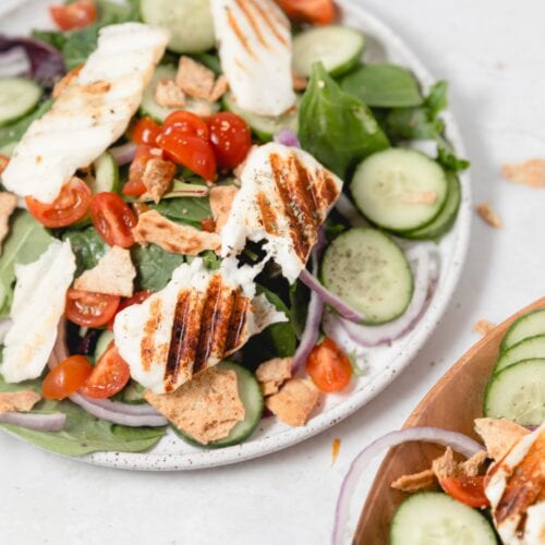 white plate with a sliced of grilled Halloumi on mixed greens