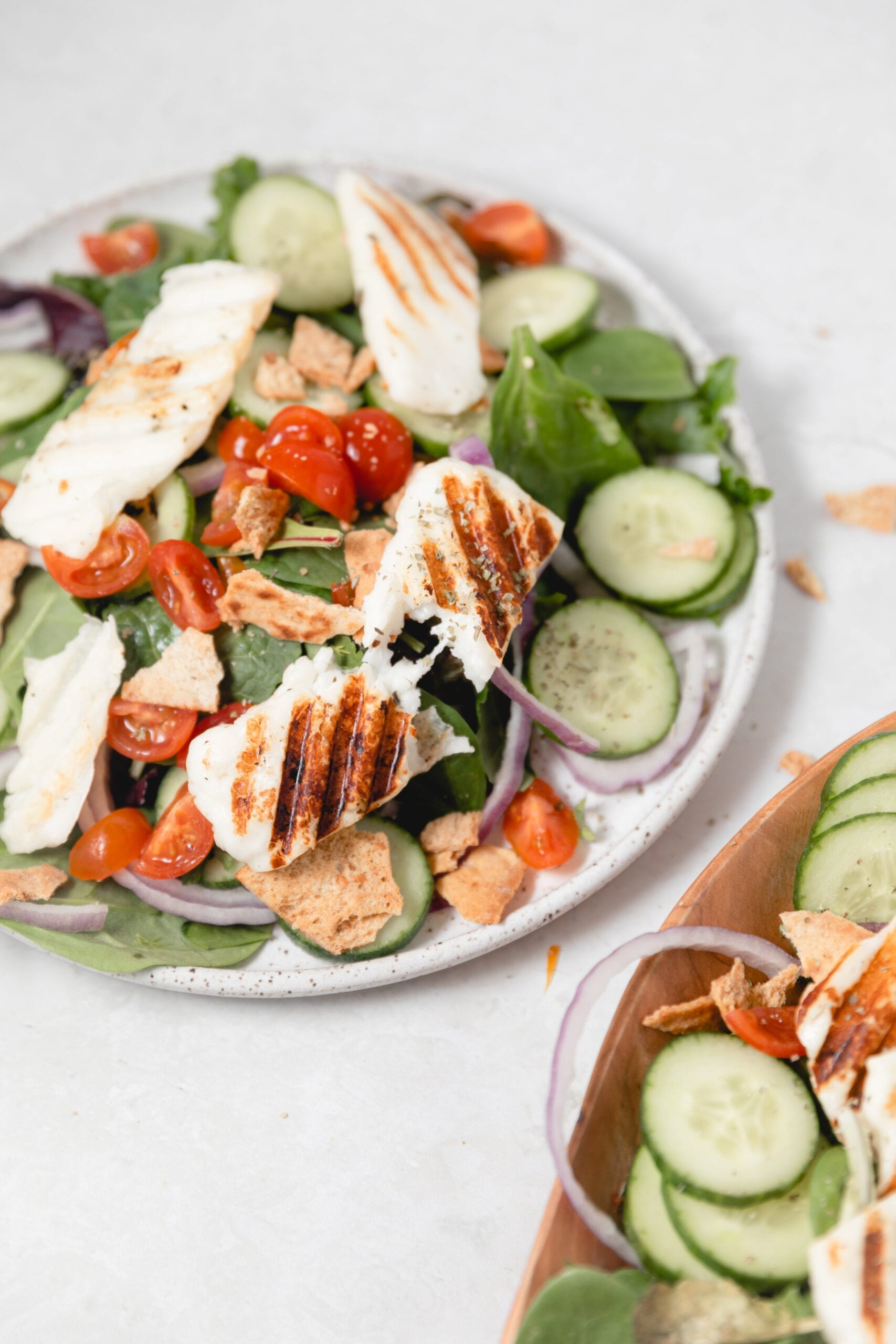 a piece of grilled Halloumi cheese pulled in half on a mixed greens salad