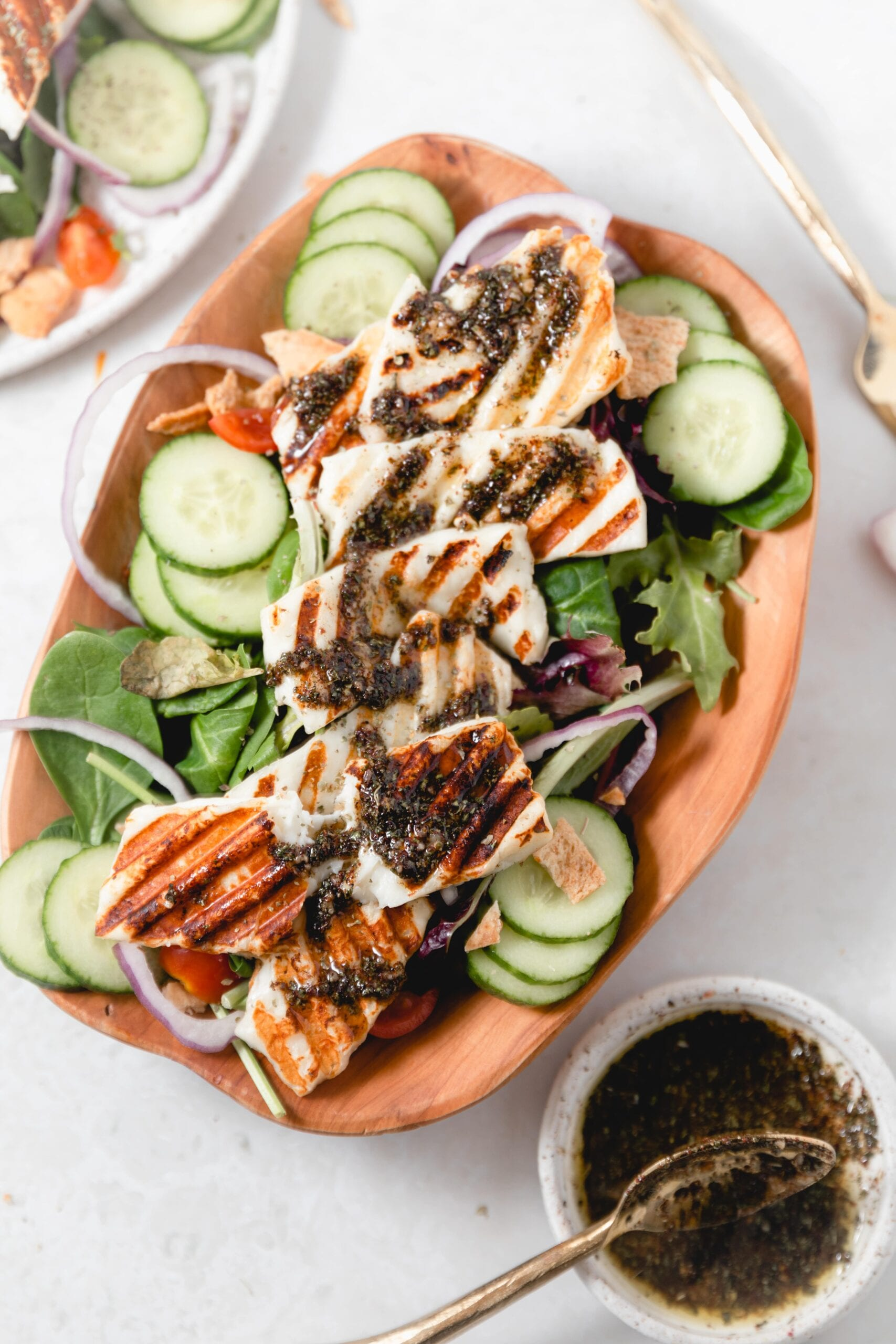 wooden bowl with grilled Halloumi Salad topped with dressing
