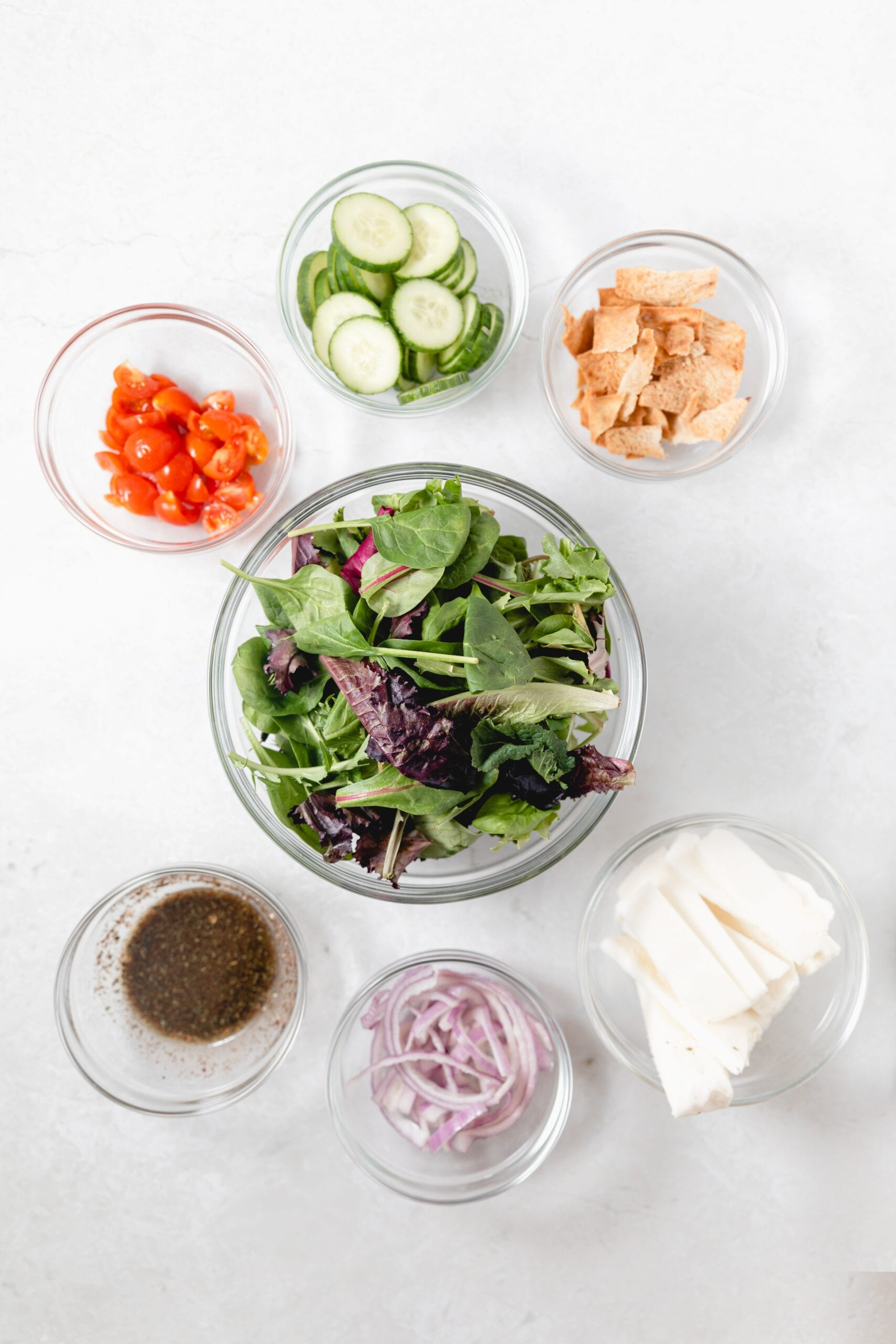 Ingredients for halloumi salad in glass bowls