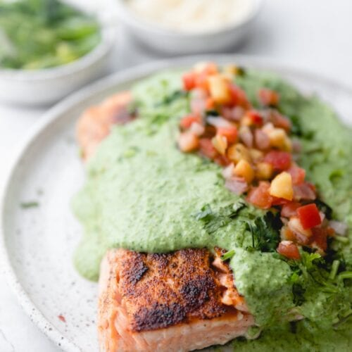 plate of salmon covered in creamy poblano sauce and topped with pico
