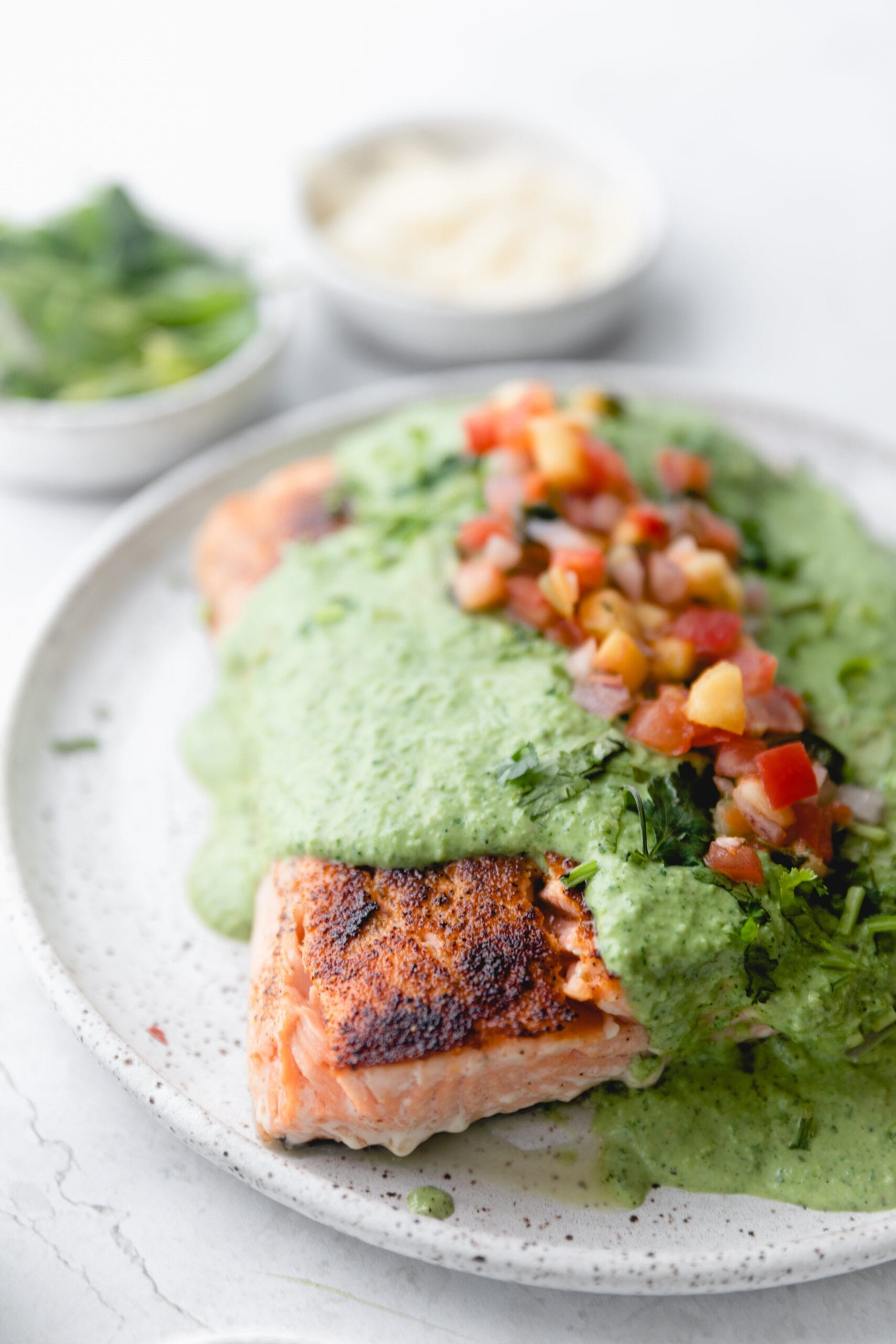 plate of salmon covered in poblano sauce and topped with pico.