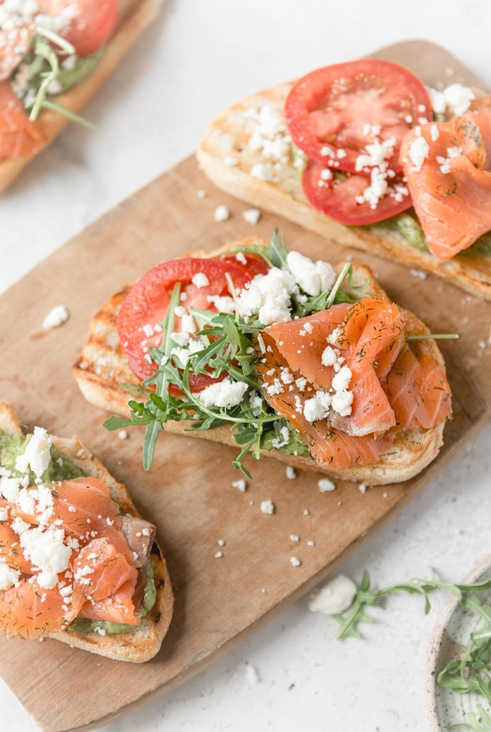 close up on salmon toast with arugula and feta