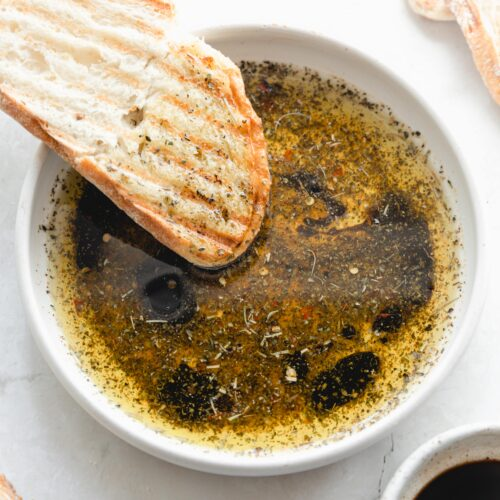 white bowl with bread dipping oil and crusty bread dipping in it