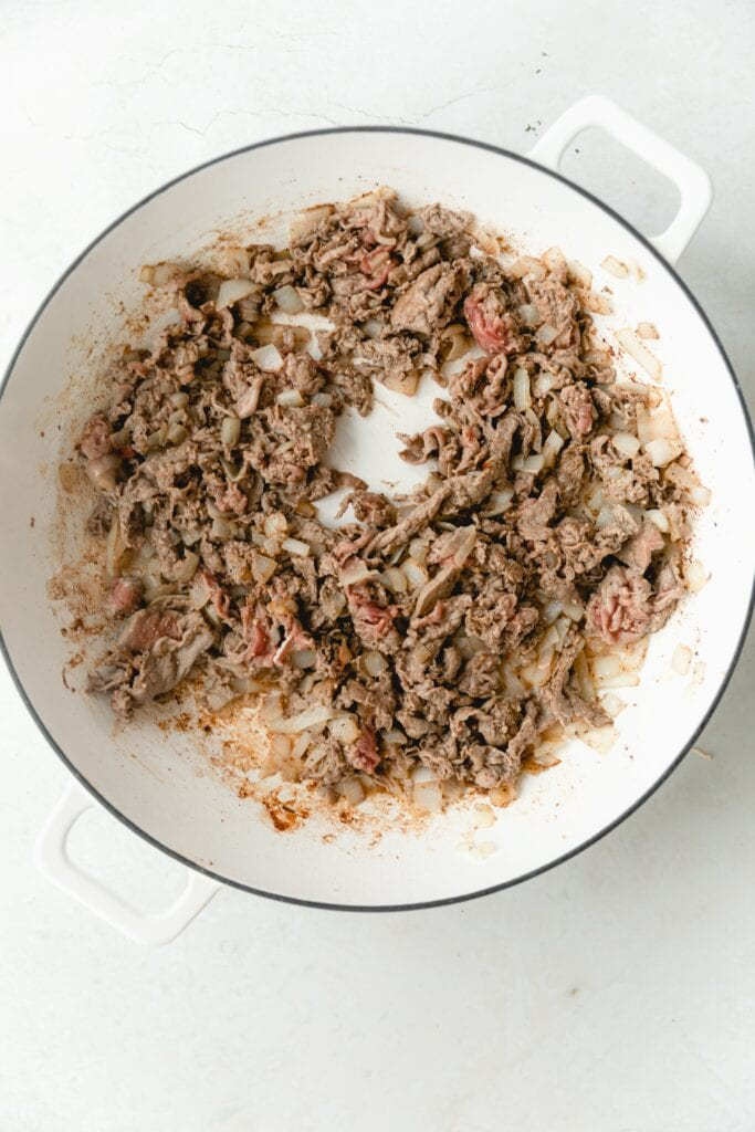 shaved steak in a white pan