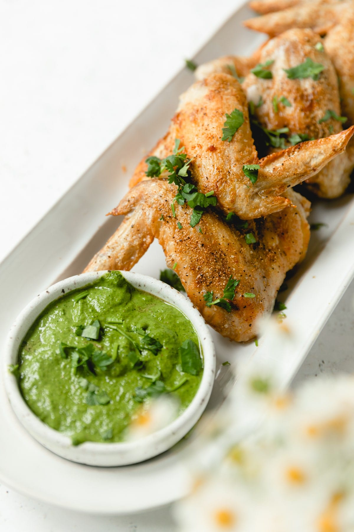 Crispy air fried wings on a white plate with chimmichurri sauce