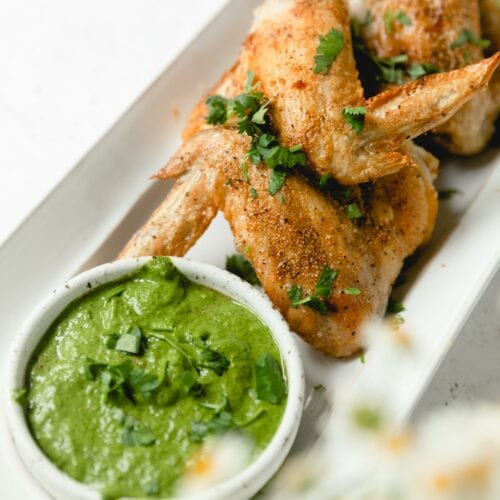 White plate with wings and side sauce of Chimichurri