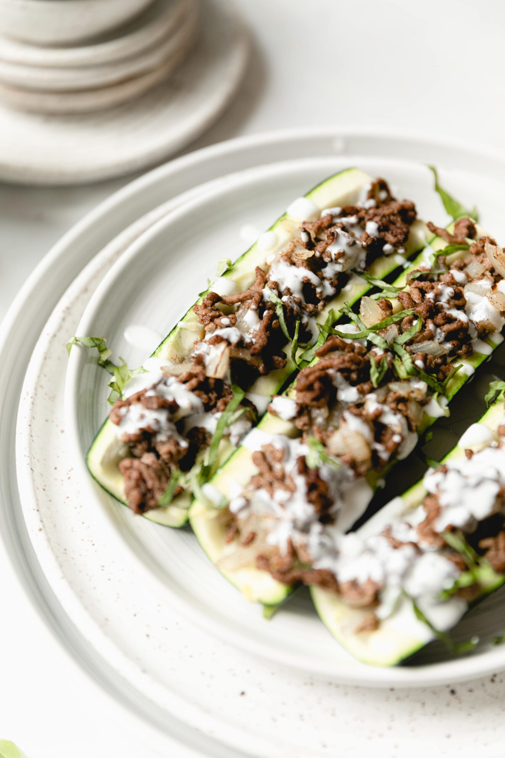 beef stuffed courgettes on a white plate