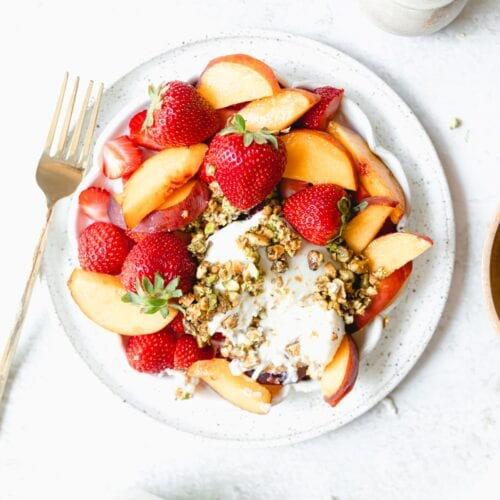 white plate of fruit with burrata cheese and pistachios
