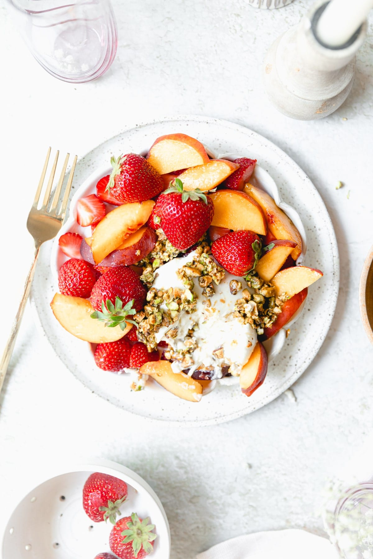 white plate full of strawberries and peaches served with burrata cheese