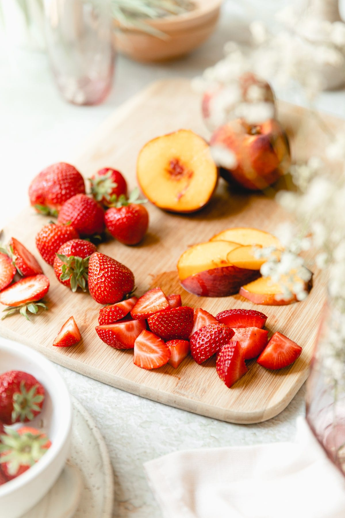 cut strawberries and peaches on a wooden cutting board
