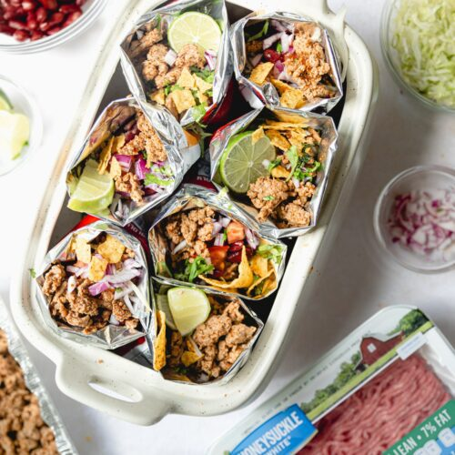 walking tacos bags in a white dish surrounded by ingredients