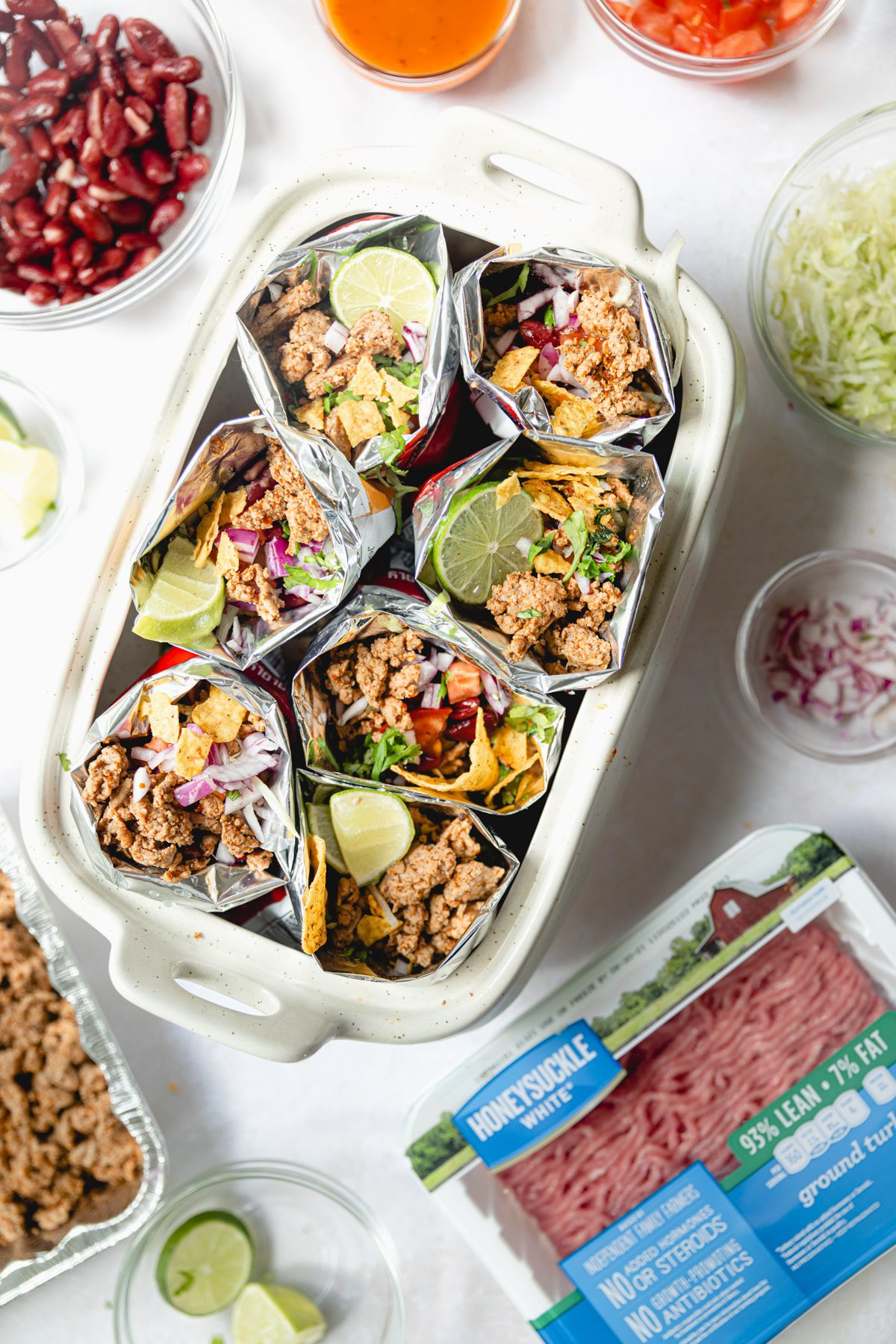 ground turkey walking tacos with toppings in a white dish