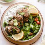 bowl of greek meatballs with salad and yogurt sauce