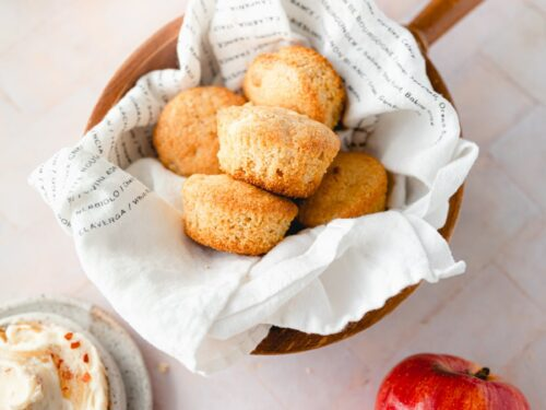 wooden bowl of cornbread muffins lined with a tea towel