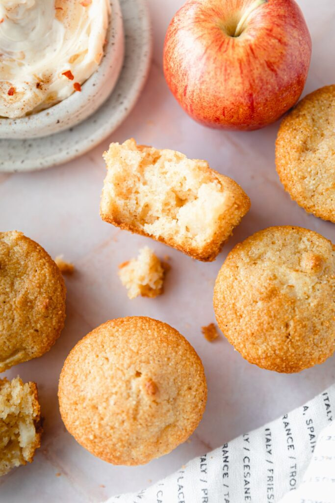 Apple cinnamon cornbread muffins with a bite taken out of one